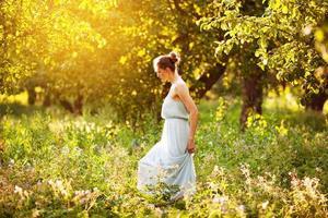 mujer en un vestido camina en un huerto de manzanas foto