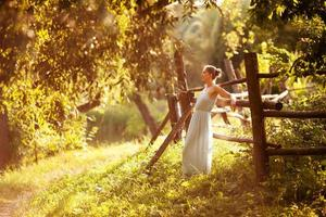 Young woman is leaning against the hedge in the evening in the garden photo