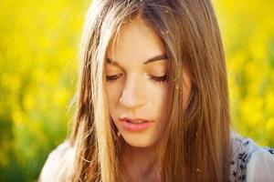 hermosa chica con cabello largo en flores amarillas foto