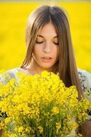 mujer joven, con, un, ramo, de, amarillo, flores silvestres foto