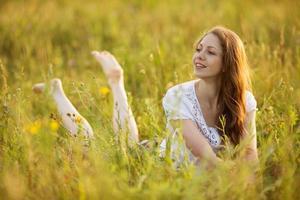 joven mujer feliz mira fuera de la hierba foto