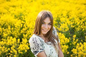 Bella mujer entre flores amarillas en un campo foto