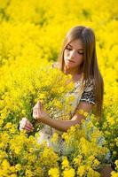 hermosa chica con un ramo de flores en el campo foto