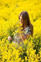 Girl in the field of yellow flowers photo