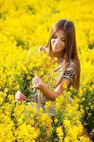 niña recoge un ramo de flores silvestres amarillas foto