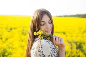 niña disfrutando del olor de las flores silvestres foto