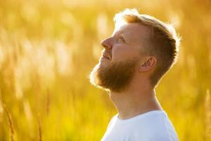 Man with a red beard looks up photo