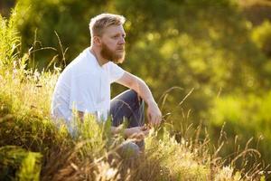 chico sentado en la hierba foto