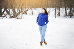 chica en una chaqueta y jeans camina foto