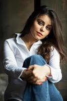 Beautiful dark-haired young woman in jeans photo
