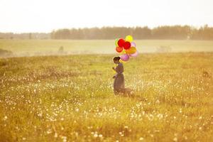 joven mujer feliz con globos en un campo foto