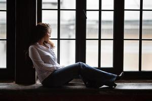 hermosa niña se sienta en la ventana y mira foto