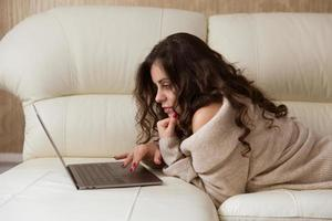 Woman is lying with a small laptop photo