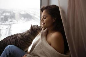 Girl and a big cat by the window photo