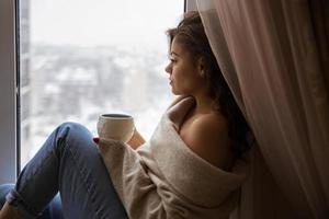 chica en la ventana con una taza de café foto