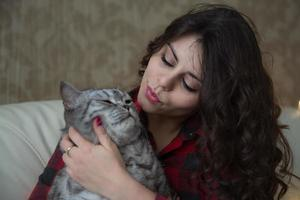 Dark-haired young woman with a big cat photo