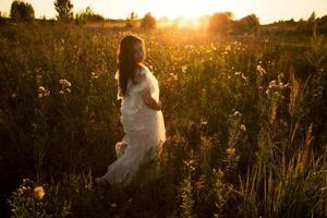 Girl in a dress walks in the evening at sunset photo