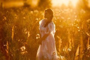 mujer caminando en el prado al atardecer foto