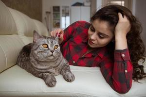 hermosa niña está acostada en el sofá con un gato grande foto