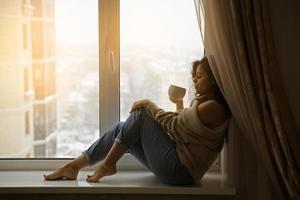 mujer en la ventana tomando cafe foto