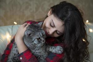 Young woman with a big gray cat photo