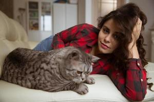 Beautiful woman is lying on the sofa with a big cat photo
