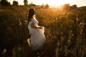 Girl in a dress walks in the evening on the field photo