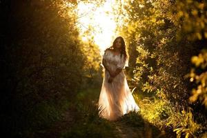 Beautiful woman in a white dress at sunset photo