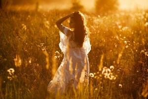 Girl stands in a field at sunset photo