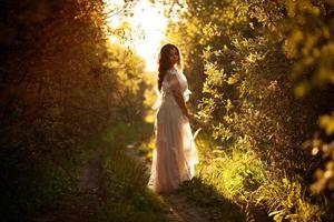 Young woman in a dress at sunset photo