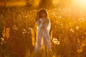 Girl walking in the meadow at sunset photo