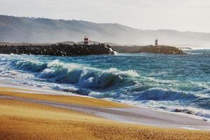 Lighthouse stands on the coastal strip of the ocean photo
