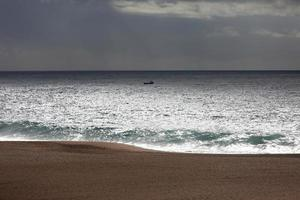 Landscape with a small boat in the ocean photo