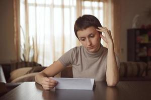 niña triste leyendo una carta foto
