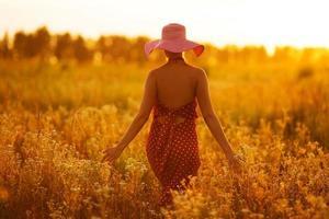 Mujer con sombrero caminando por campos de flores. foto