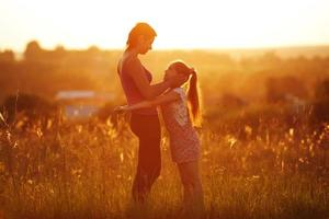 Happy mother and daughter in a field photo