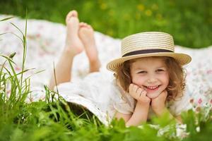 niña feliz en un sombrero miente y se ríe foto
