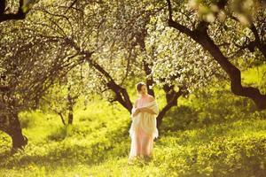 mujer está de pie entre flor de manzano foto