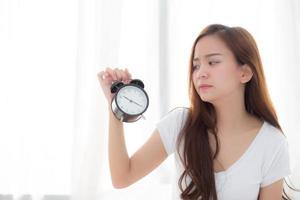 joven mujer asiática se despierta en la mañana molesto despertador de la mano. foto