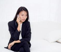 Young asian woman talking phone in the living room. photo
