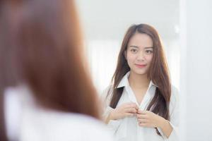 Young asian woman examining with face and smile looking on mirror. photo