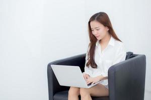 mujer asiática joven que usa la computadora portátil para el ocio en el sofá. foto