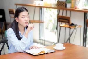 joven asiática pensando idea y escribiendo en el cuaderno. foto