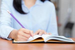 mano de mujer escribiendo en el cuaderno en la mesa. foto