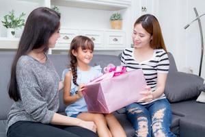 feliz de familia dando la caja de regalo con hija. foto