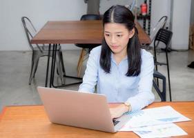 mujer asiática joven que trabaja con papel estadístico gráfico en la computadora portátil. foto