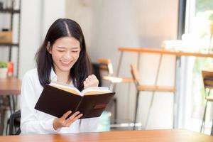 joven mujer de negocios asiática leyendo en el portátil en el escritorio. foto