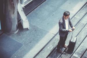 Asian businessman talking phone while walking holding suitcase. photo