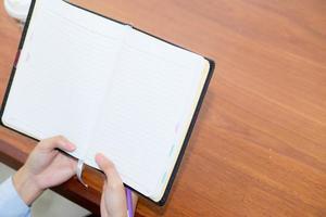 primer plano de la mano de la mujer que sostiene el cuaderno en la mesa de madera. foto