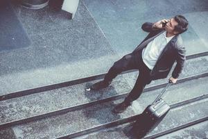 Asian businessman wear suit talking phone while holding suitcase. photo
